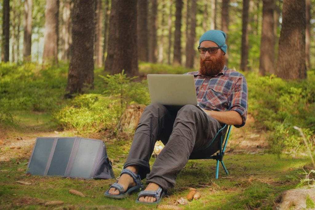 Individual sat in the woods working on a laptop with a small tent to next to them