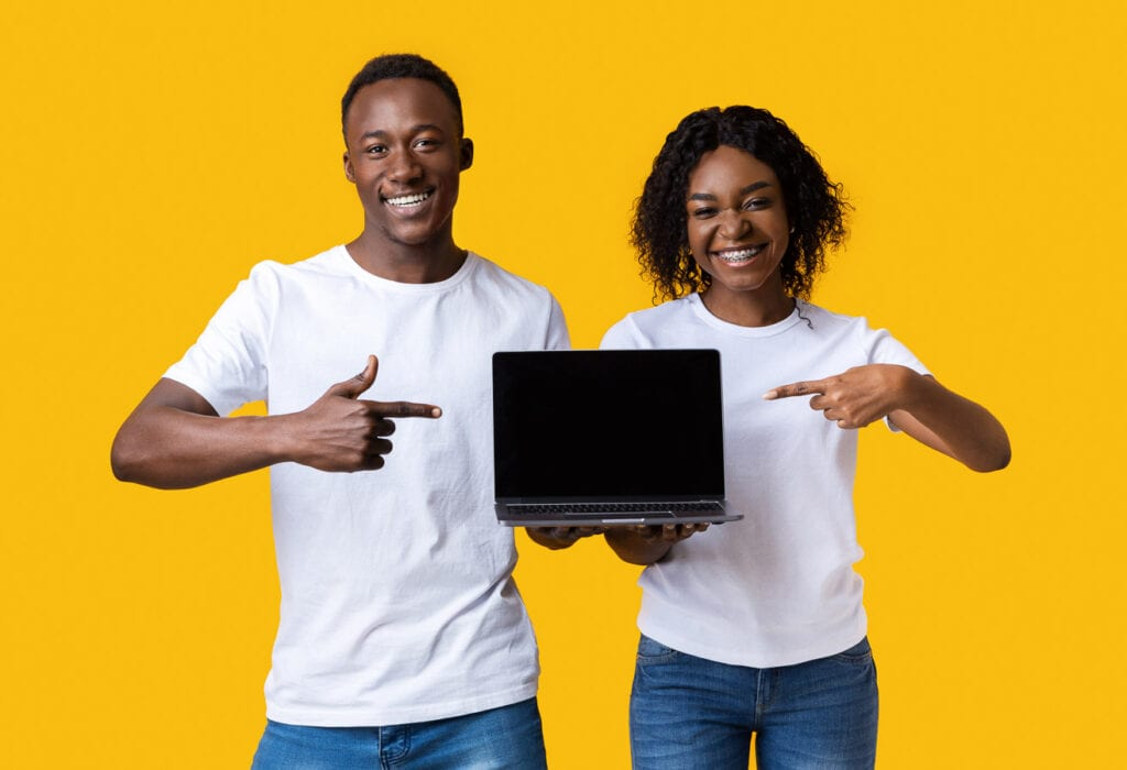 Two young black individuals pointing at blank laptop screen