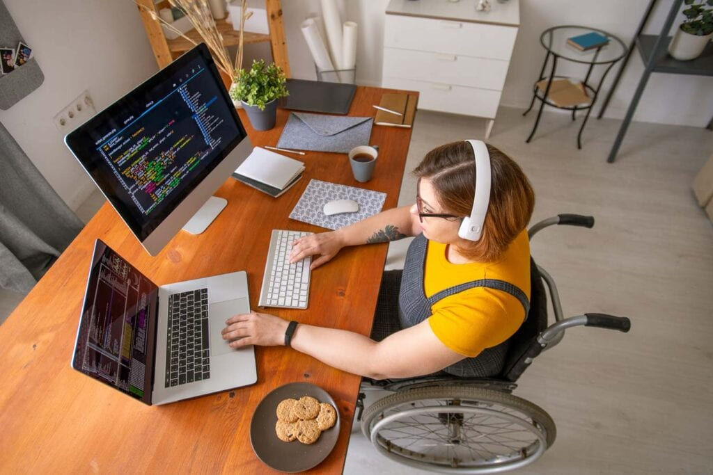 woman in wheelchair typing at a computer