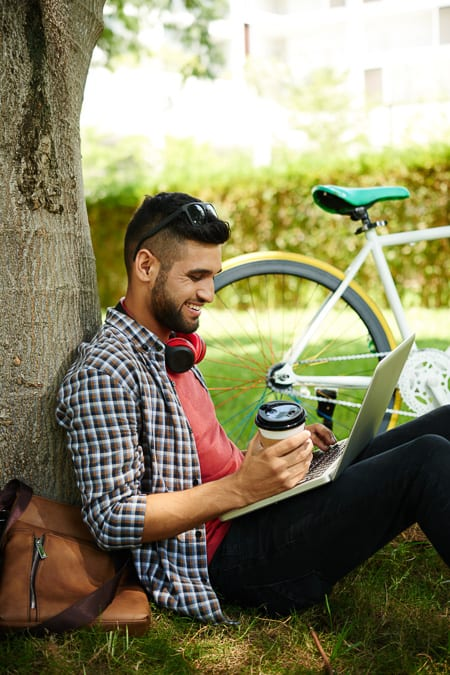 man with laptop and coffee leaning against a tree with a bike next to him