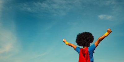 A child dressed in a superhero costume with their arms held out as if flying