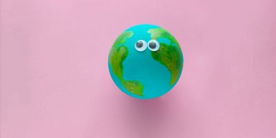 Earth planet model with googly eyes on a pastel pink background