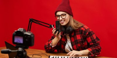 Young blogger sitting at the table playing on musical keyboard and singing in microphone she shooting video for her followers