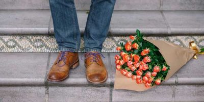 The bottom of a pair of legs in jeans and brown shoes, next to a bunch of flowers
