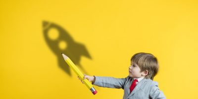Happy child holding pencil against yellow background