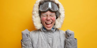 frost covered woman in parka screaming excitedly